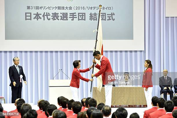 Japan delegation chief Seiko Hashimoto hands the flag to a flag-bearer Keisuke Ushiro of Japan during the send-off event for the Japanese national...