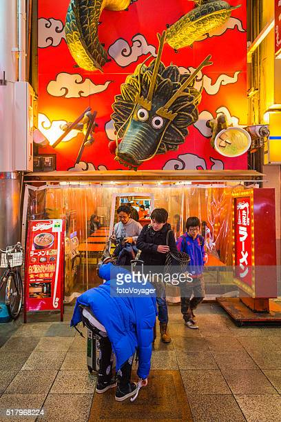 Japan diners leaving a dragon themed restaurant Dotonbori nightlife Osaka
