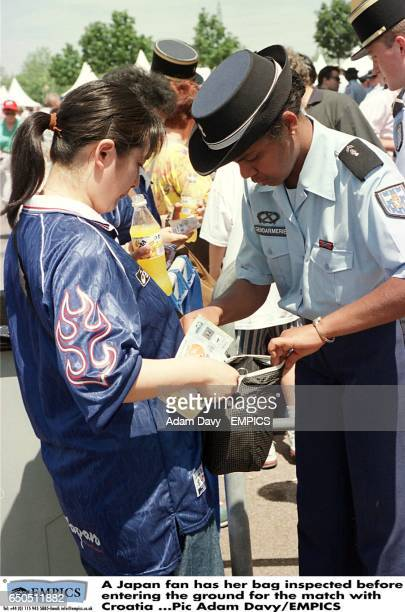 A Japan fan has her bag inspected before entering the ground for the match with Croatia