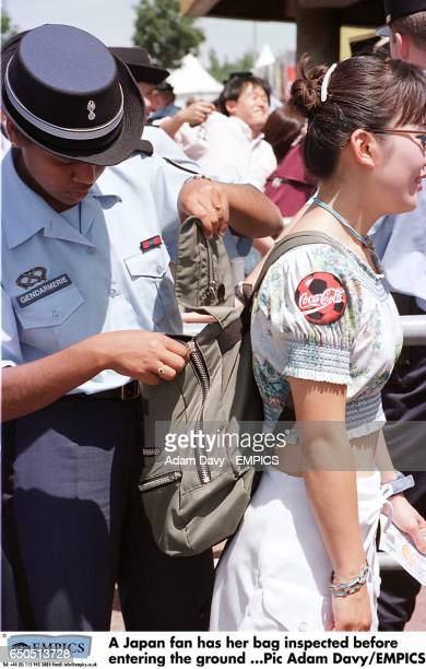 A Japan fan has her bag inspected before entering the ground