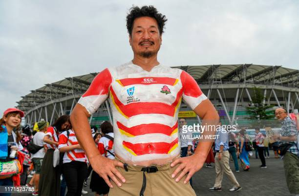 A Japan fan has the national team's jersey painted on as he arrives for the Japan 2019 Rugby World Cup Pool A match between Japan and Ireland at the...