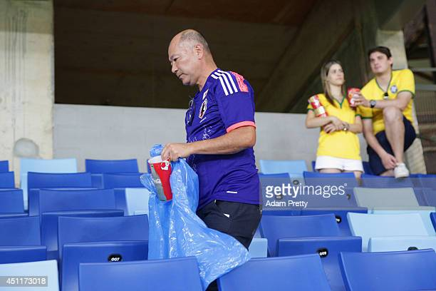 Japan fan helps collect litter from the stadium after the 2014 FIFA World Cup Brazil Group C match between Japan and Colombia at Arena Pantanal on...