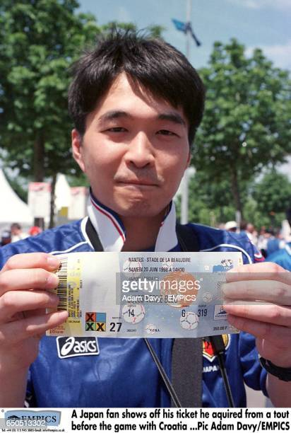 A Japan fan shows off his ticket he aquired from a tout before the game with Croatia