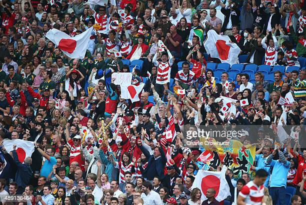Japan fans celebrate their team's surprise victory during the 2015 Rugby World Cup Pool B match between South Africa and Japan at the Brighton...