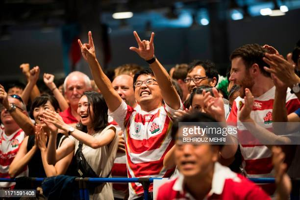 TOPSHOT Japan fans cheer for their team as they watch the Japan 2019 Rugby World Cup Pool A match between Japan and Ireland at a fanzone area in...