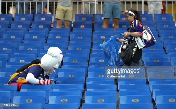 Japan fans collect rubbish from the stands following their sides defeat in the 2018 FIFA World Cup Russia Round of 16 match between Belgium and Japan...
