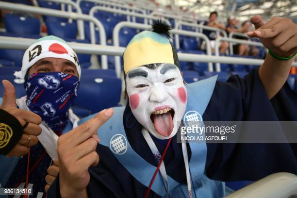 TOPSHOT Japan fans pose in the stands ahead of the Russia 2018 World Cup Group H football match between Japan and Poland at the Volgograd Arena in...