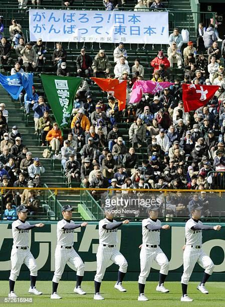 NISHINOMIYA Japan Fans raise a banner to cheer on the marching baseball players of Tohoku High School from quakehit Miyagi Prefecture northeastern...