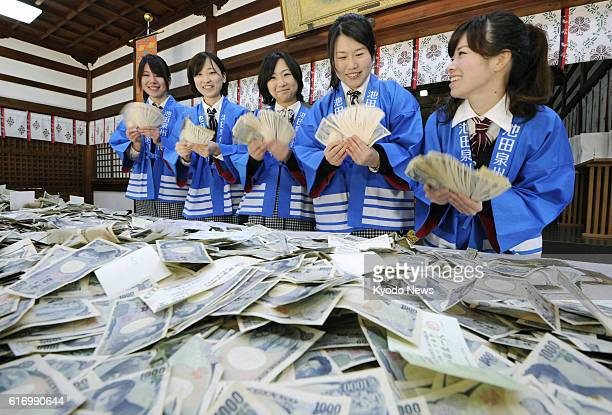 OSAKA Japan Female bank staffers wearing traditional Japanese happi coats count money given as offerings during the annual ''Toka Ebisu'' festival at...