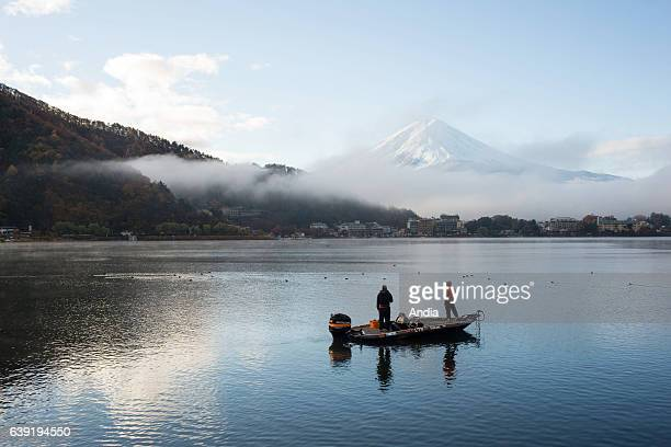 fishermen on Kawaguchiko lake in FujiHakoneIzu national park in Chubu area on Honshu island in the background mount Fujit