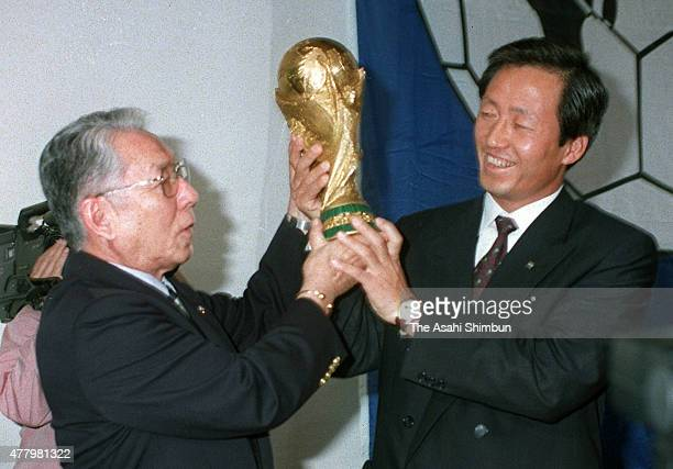 Japan Football Association President Ken Naganuma and South Korean Football Association President Chung Mongjoon lift the World Cup after the 2002...