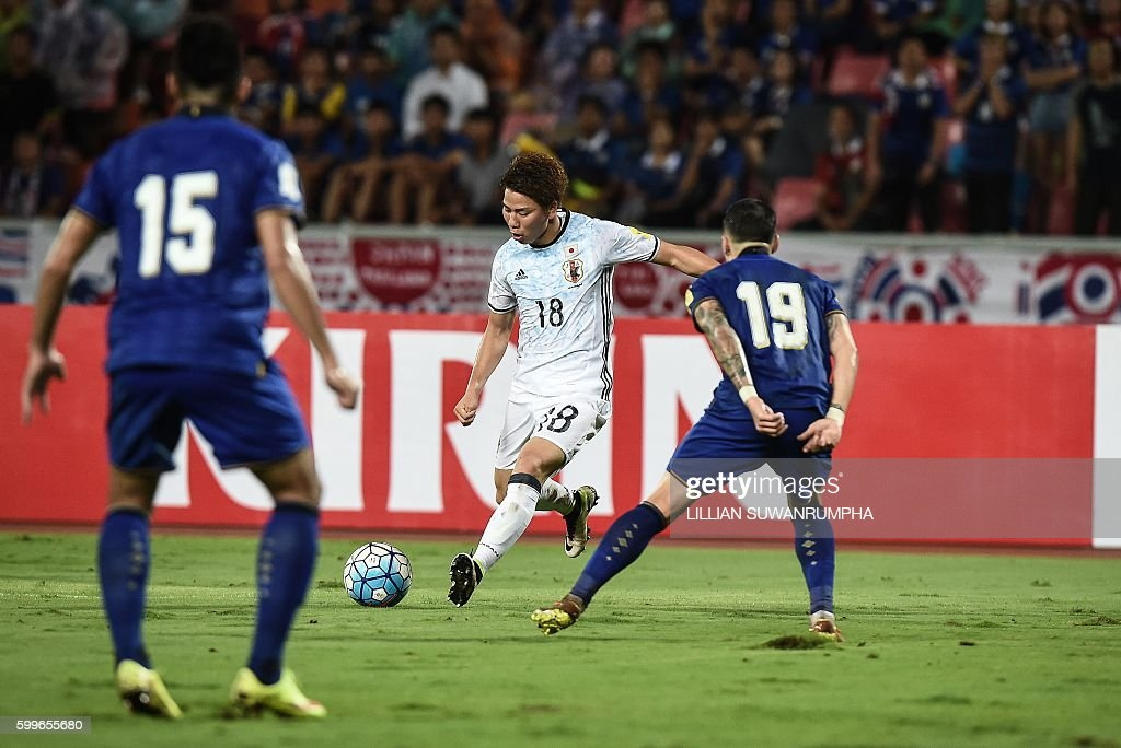 Japan football player Takuma Asano (C) makes an attempt on goal during the 2018 FIFA World Cup qualifying match between Thailand and Japan in Bangkok on September 6, 2016. / AFP / LILLIAN