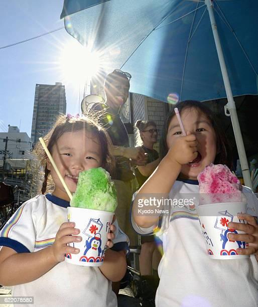 OSAKA Japan Girls hold shaved ice under the blazing sun in Osaka on July 10 2013