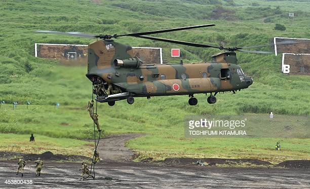 Japan Ground Self Defense Forces' personnels jump from a CH47 helicopter during an exercise in its HigashiFuji training ground in Gotemba some 100...
