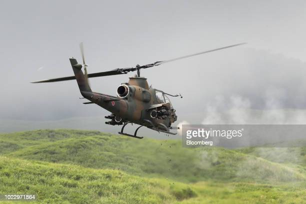 A Japan Ground SelfDefense Force AH1S Cobra attack helicopter fires during a live fire exercise at the foot of Mount Fuji in the Hataoka district of...