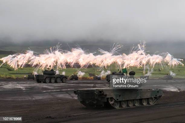 Japan Ground SelfDefense Force battle tanks and vehicles fire smoke rounds during a live fire exercise at the foot of Mount Fuji in the Hataoka...