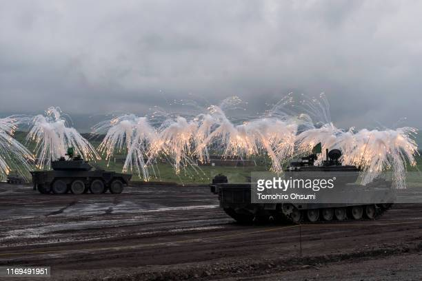 Japan Ground Self-Defense Force battle tanks fire smoke rounds during a live fire exercise at the foot of Mount Fuji in the Hataoka district of the...