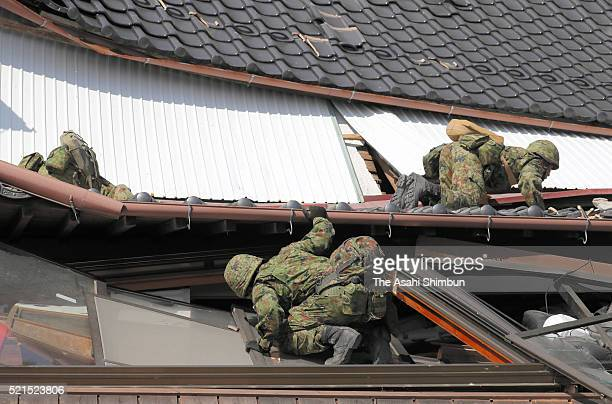 Japan Ground SelfDefense Force members check a collapsed house as the rescue operation continues on April 16 2016 in Minamiaso Kumamoto Japan The...