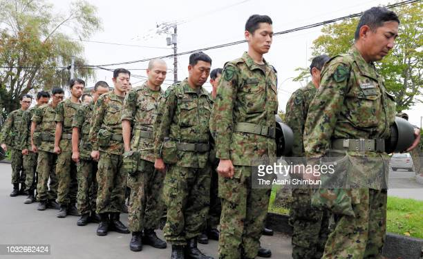 Japan Ground SelfDefense Force members observe a minute of silence at Atsuma City Hall a week after the magnitude 67 earthquake on September 13 2018...