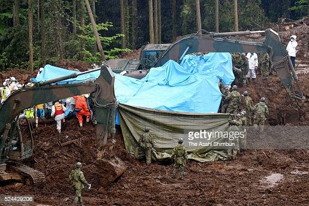 Japan Ground Self-Defense Force members recover a body of victim at a landslide site on April 25, 2016 in Minamiaso, Kumamoto, Japan. 49 people have...