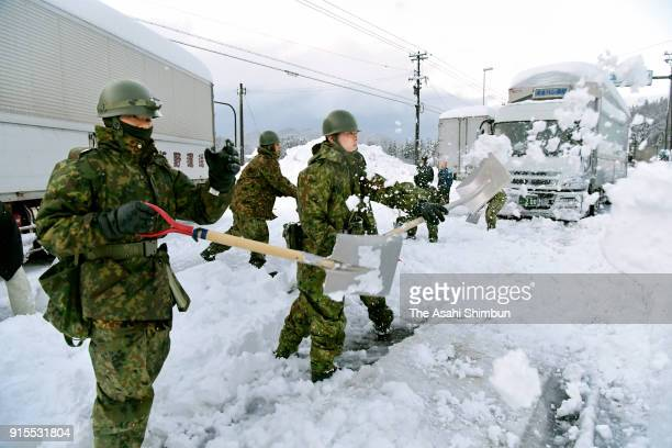 Japan Ground SelfDefense Force members remove snow as heavy snow brings traffic to a standstill on National Route No 8 on February 7 2018 in Sakai...