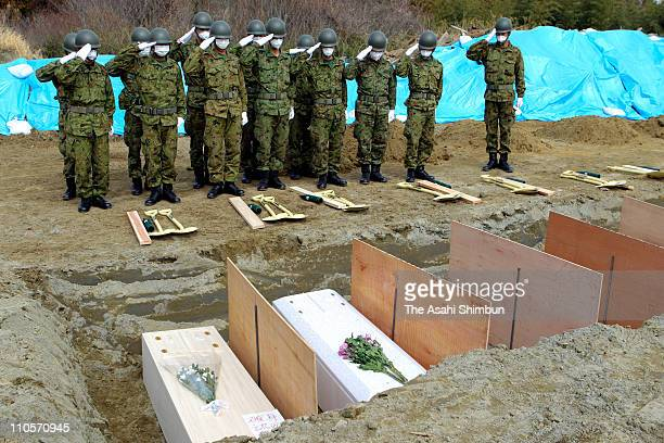 Japan Ground SelfDefense Force personnel salute coffins of victims of the March 11 Japan earthquake and tsunami during a burial ceremony at a...