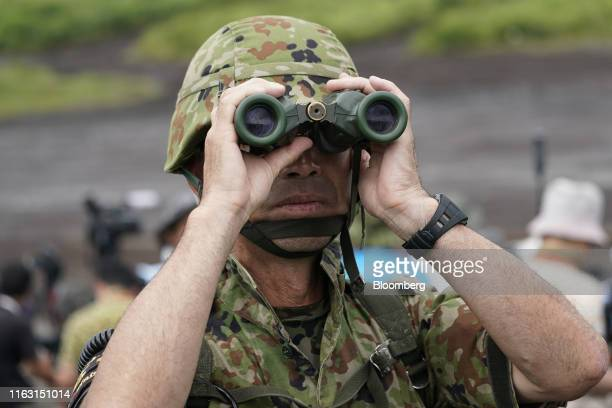 Japan Ground Self-Defense Force soldier uses a binocular during a live fire exercise in the Hataoka district of the East Fuji Maneuver Area in...