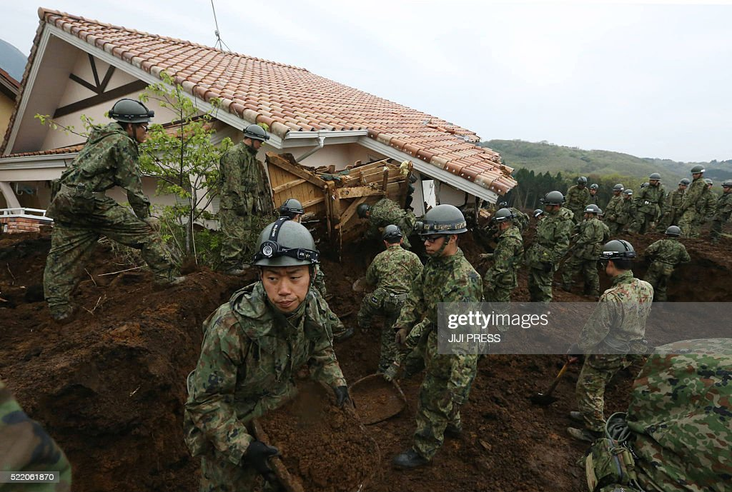 Japan Ground Self-Defense Force troops search for victims buried due to the recent earthquakes in the village of Minami-Aso in Kumamoto prefecture on April 18, 2016. Rescuers intensified efforts on April 18 to find 10 people still missing in a devastated village, with time running out more than two days after Japan's double quake disaster which unleashed landslides and collapsed buildings. / AFP / JIJI PRESS / JIJI PRESS / Japan OUT