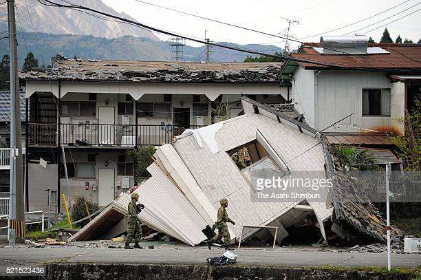 Japan Ground SelfDefense Force walk in front of collapsed buildings as the rescue operation continues on April 16 2016 in Minamiaso Kumamoto Japan...