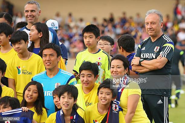 Japan head coach Alberto Zaccheroni watches on as the team pose for a group photo with children from the local community during a Japan training...