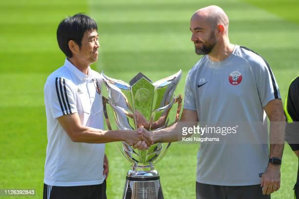 Japan Head coach Hajime Moriyasu and Qatar head coach Felix Sanchez Bas pose for photographs with Asian Cup trophy on January 31 2019 in Abu Dhabi...