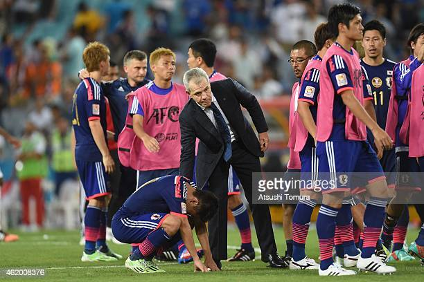 Japan Head coach Javier Aguirre helps Shinji Kagawa stand up after Japan lose the penalty shoot out over United Arab Emirates during the 2015 Asian...