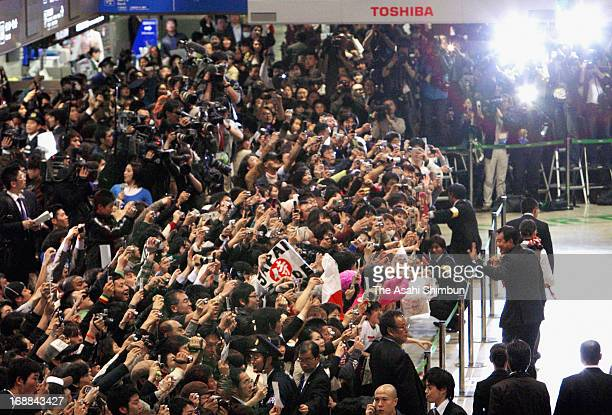 Japan head coach Tatsunori Hara waves to supporters upon arrival after winning the World Baseball Classic at Narita International Airport on March 25...