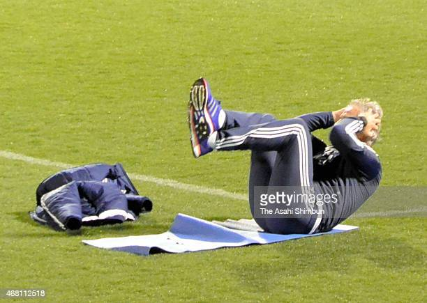 Japan head coach Vahid Halilhodzic does sit-ups during a training session at Nishigaoka Stadium on March 29, 2015 in Tokyo, Japan.