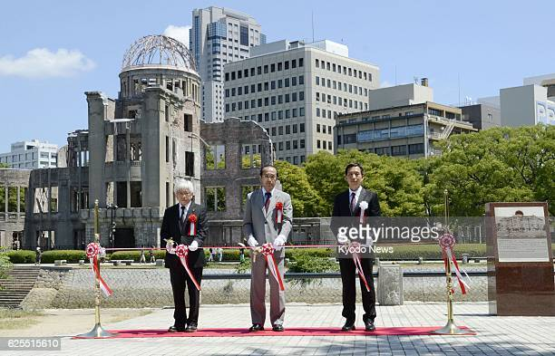 HIROSHIMA Japan Hiroshima Mayor Kazumi Matsui cuts the ribbon during a ceremony with the Atomic Bomb Dome in the background in the city of Hiroshima...