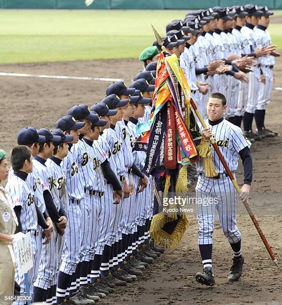 NISHINOMIYA Japan Hirotsugu Sato captain of Tokaidai Sagami in Kanagawa Prefecture carries the champion flag at Koshien Stadium in Hyogo Prefecture...