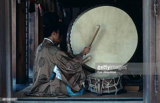 Japan Honshu Shimane Izumo Priests striking large drum during worship at IzumoTaisha one of the oldest Shinto shrines in the country dedicated to...