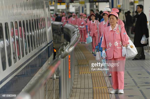 Japan Honshu Tokyo A cleaning crew of middle aged women in uniform wait to board a bullet train shinkansen to clean it