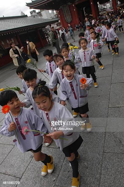 Japan, Honshu, Tokyo, Asakusa. 4 year old nursery students from Senso-ji Dembo-in Nursery, carrying flowers to present to Buddha on his birthday...