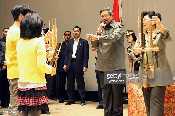 KESENNUMA Japan Indonesian President Susilo Bambang Yudhoyono and his wife Kristiani Herawati teach children how to play an angklung a musical...
