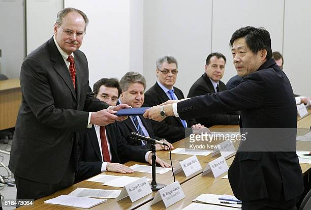 TOKYO Japan James Lyons nuclear installation safety director of the International Atomic Energy Agency's Nuclear Installation Safety Division hands a...