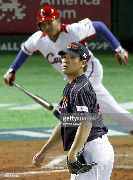 Japan - Japan pitcher Masahiro Tanaka watches the ball after Cuba's Frederich Cepeda hits an RBI double in the fourth inning of a World Baseball...
