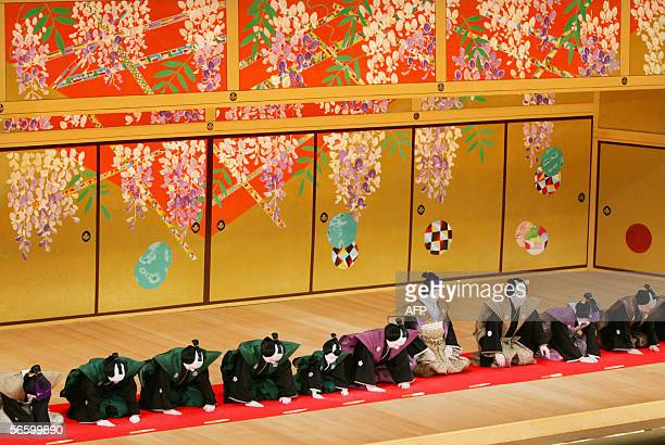 "Japanese kabuki actor Tojuro Sakata , flanked by performers, bows as he greets the audience during his kabuki stage ""Kojo"" to mark his succession to..."