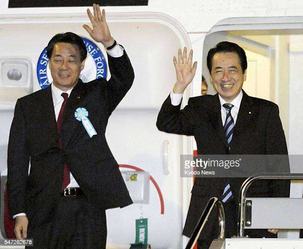 TOKYO Japan Japanese Prime Minister Naoto Kan and Banri Kaieda minister of economy trade and industry wave as they depart from Tokyo on Jan 28 for...