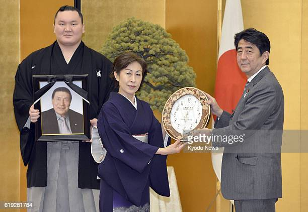 TOKYO Japan Japanese Prime Minister Shinzo Abe hands a commemorative gift to Yoshiko Naya the widow of the late yokozuna Taiho during a ceremony in...