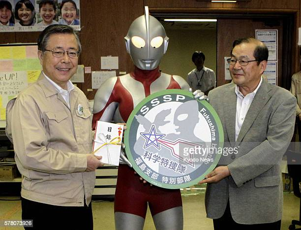 Japan - Japanese television series hero Ultraman and Shinichi Ooka , president of the series' producer Tsuburaya Productions Co., hands a 2 million...