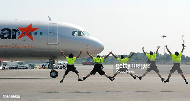 NARITA Japan Jetstar Japan Co employees perform a star jump as they see off the first flight of the budget airline funded by Japan Airlines Co from...