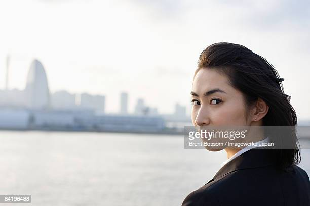 Japan, Kanagawa Prefecture, Yokohama City, Business woman standing by river, smiling, portrait, skyline in background