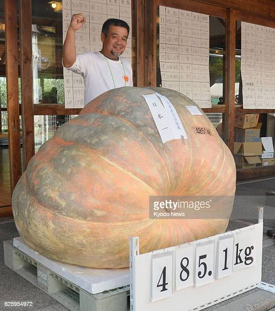 TAKAMATSU Japan Koji Ueno celebrates behind the 4851kilogram pumpkin he grew after it was declared Japan's heaviest in a national competition on...
