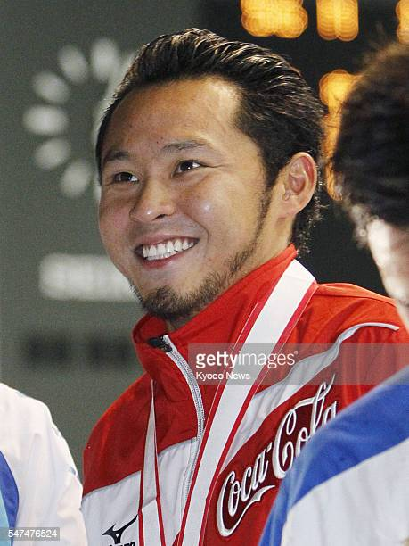 TOKYO Japan Kosuke Kitajima smiles after winning the men's 100meter breaststroke with a national record at the shortcourse national championships in...